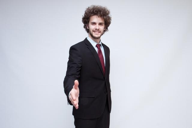 握手を求めるスーツ姿の男性