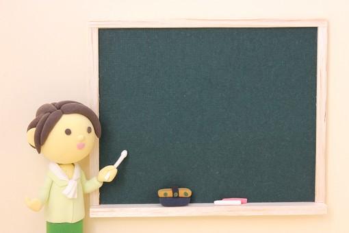 黒板をさす女の人の粘土人形