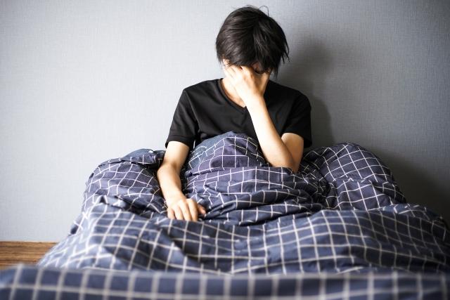 ベッドで悩む男性の写真
