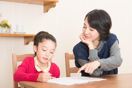 子どもの勉強をみるお母さんの写真