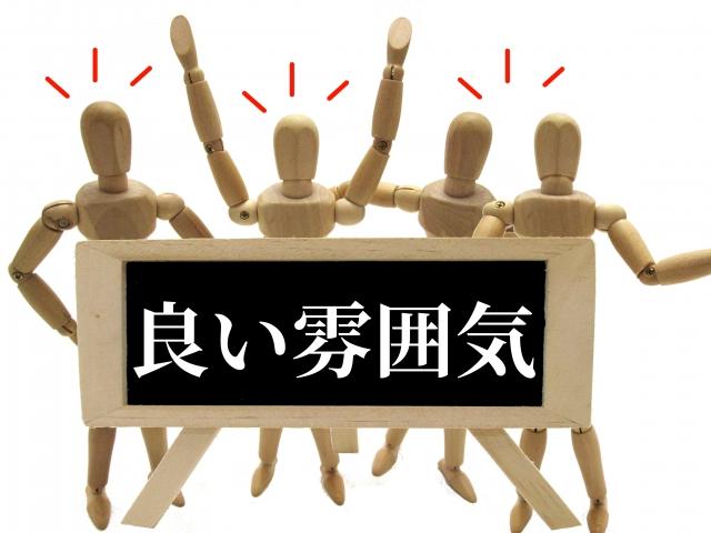 良い雰囲気というボードを掲げた木の人形