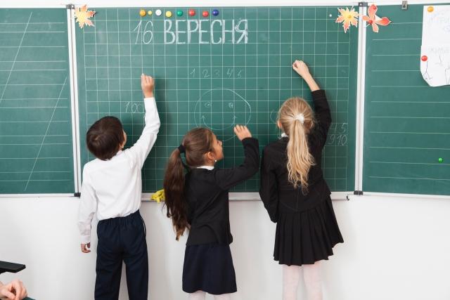 黒板に字を書く子どもたち