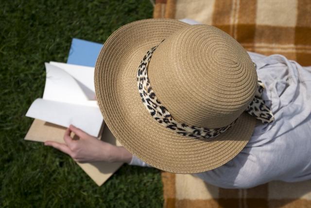 帽子をかぶって読書をする人の写真