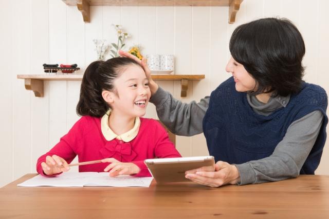 娘の宿題をみるお母さんの写真